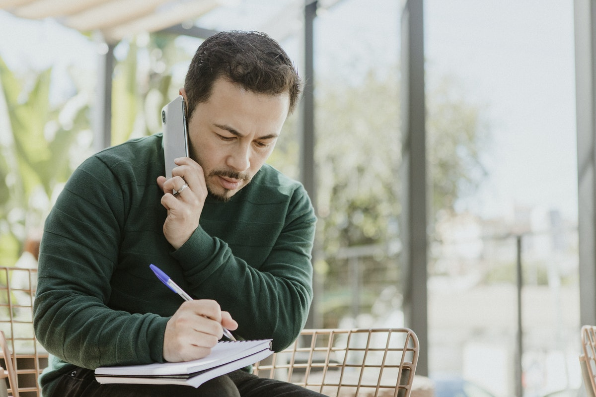 Man taking a phone call while taking notes