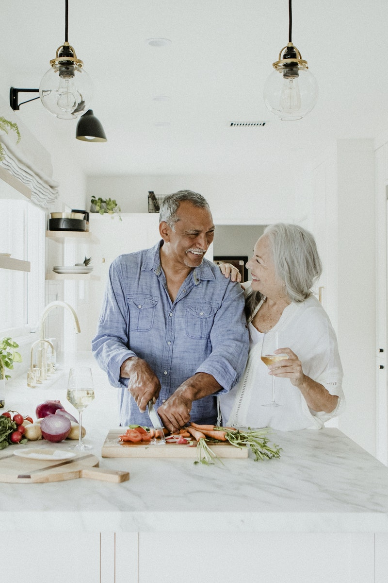 Couple laughing while cutting vegetables in kitchen