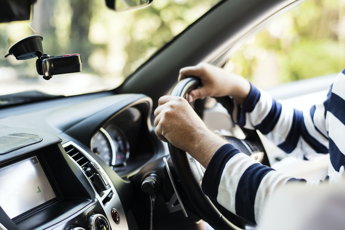 Close up of someone with their hands on a steering wheel