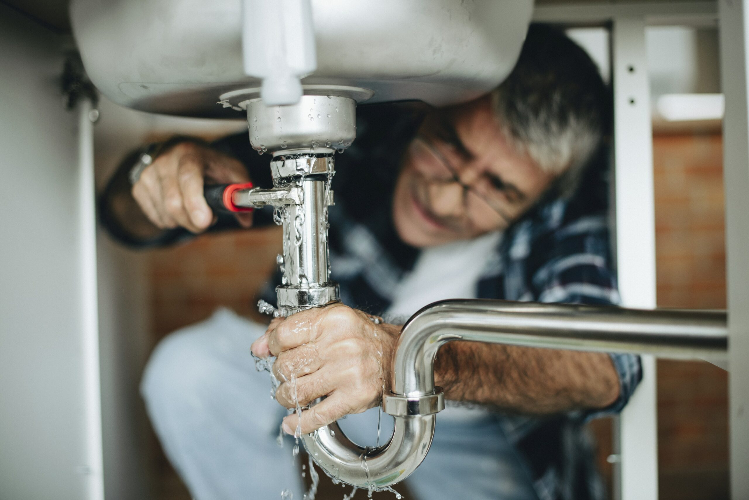 Man trying to fix leaking pipes below sink