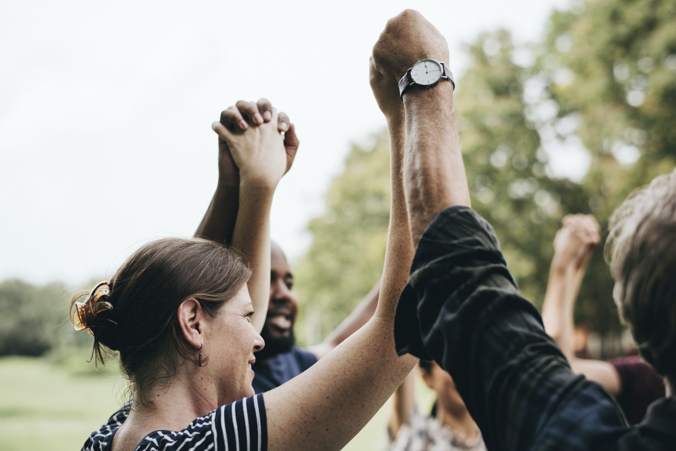 Group of people with intertwined hands in the air