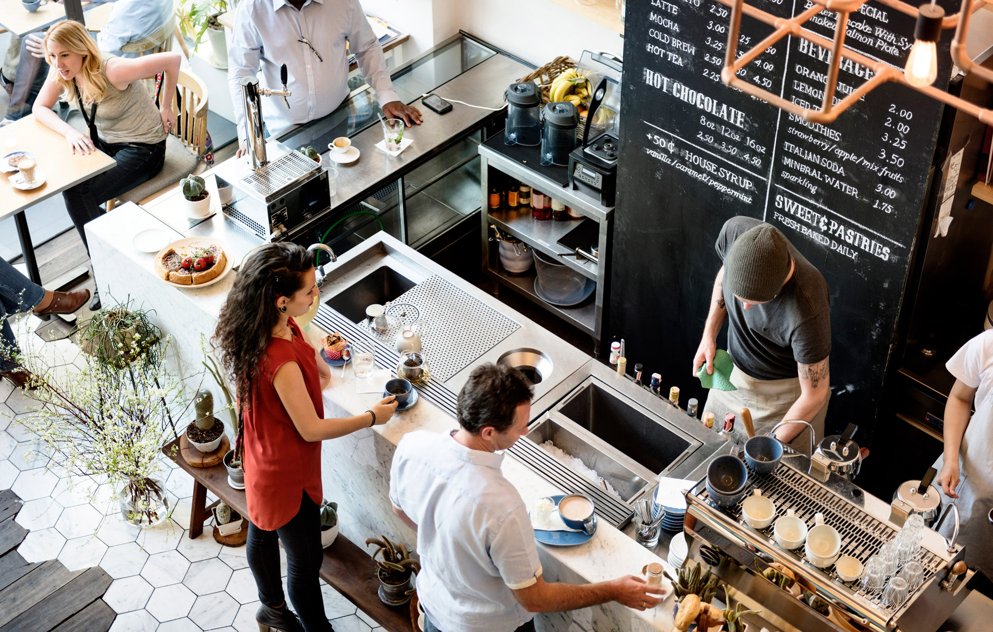 Overhead image of customers ordering drinks at a coffee bar