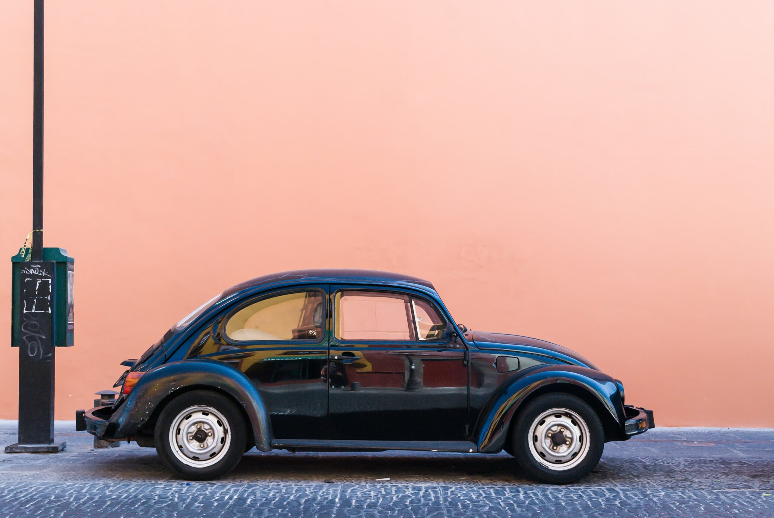 Volkswagon beatle against a pink wall background